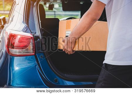 Delivery Man Is Delivering Cardboard Box To Customers Via Private Car Trunk Door. People Lifestyles