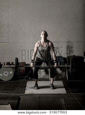 Dramatic subdued color image of strong female weight lifter with barbell.
