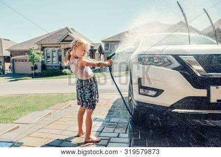 Cute Preschool Little Caucasian Girl Washing Car On Driveway In Front House On Sunny Summer Day. Kid