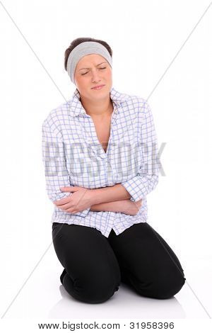A picture of a young woman sitting on the floor and suffering from stomach ache
