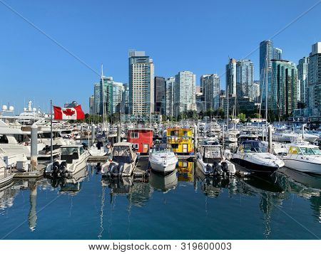 Luxury yachts and Canadian flag on a summer day in Coal Harbour, Vancouver, British Columbia, Canada.