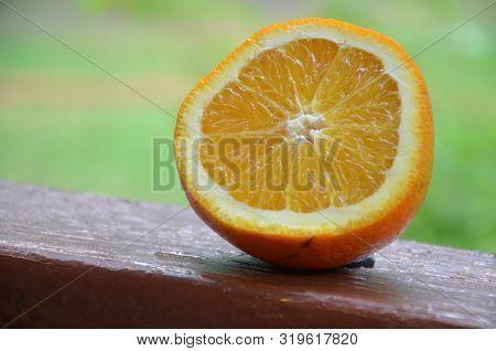 Orange, Half Of Orange, Orange Lobule And Basket With Oranges On The Wooden Table On The Green Blurr
