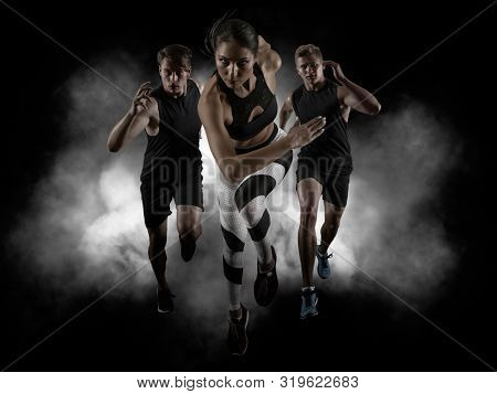 Sporty young woman and men running on black background