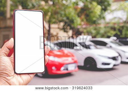 Hand Hold Blank Screen On Mobile, Cellphone, Tablet On Blurry White Car. Concept Of Find Used Card O