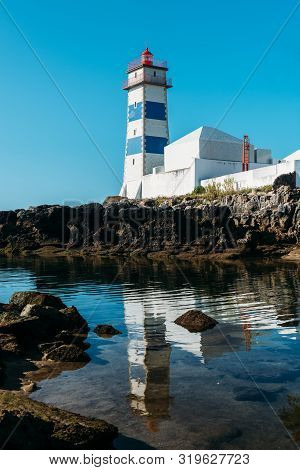 Santa Marta Lighthouse And Municipal Museum, Cascais, Lisbon, Portugal Reflected On A Stream