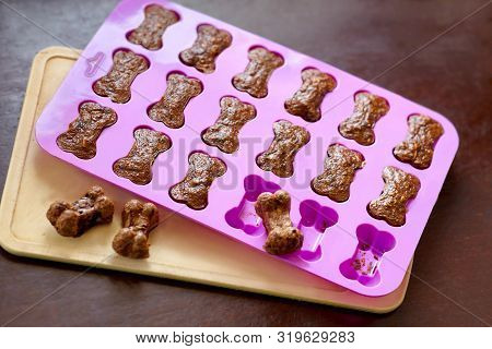 Cooking The Homemade Biscuits For Dogs, Bone-shaped In Silicone Mold, Taken Out Of The Oven. Dog Tre