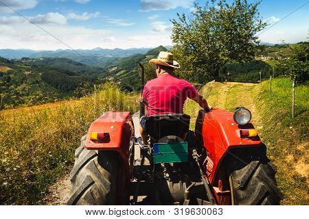 Man Driving Tractor In Agricultural Fields. Agricultural Worker Driving Tractor In Nature. Man Worki