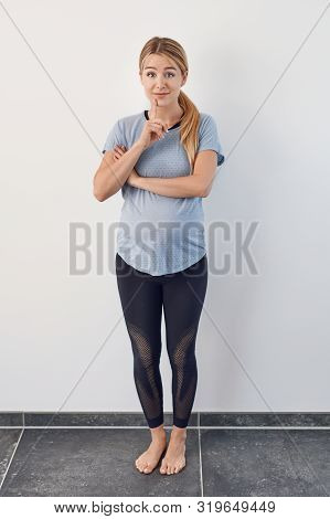 Surprised Barefoot Young Pregnant Woman Standing With Her Hand To Her Chin Raising Her Eyebrows With