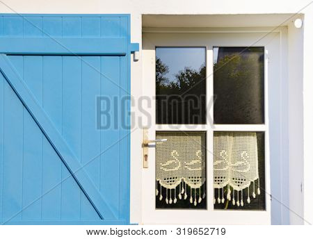 Sunny View Of A Blue Window Of An Old Farm House With Shutters, Where A Curtain Of Handmade Crochet