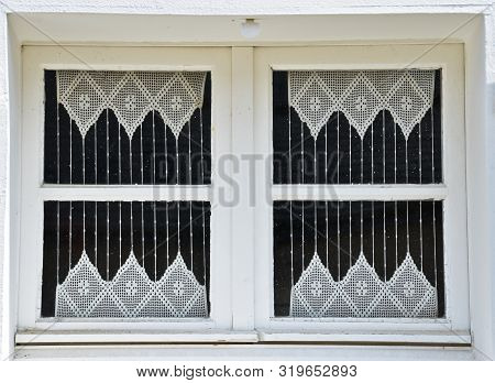 Sunny View Of A Window Of An Old Farm House With Shutters, Where A Curtain Of Handmade Crochet Hangs