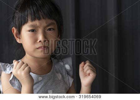 Portrait Of An Angry Asian Little Child Girl, Raised Fist.