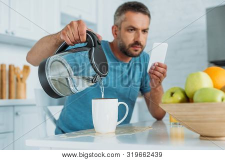 Selective Focus Of Man Overfilling Cup With Water While Sitting At Kitchen Table And Using Smartphon