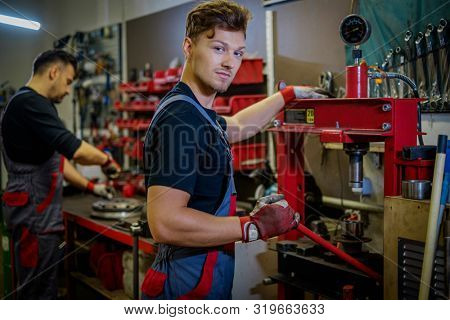 Car mechanic working on a hydraulic press in a workshop