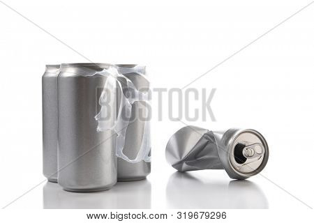 Closeup of three aluminum cans and one crushed empty can. Cans have no label.