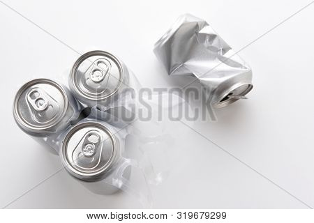 High angle shot of a three aluminum cans in plastic 6 pack carrier and one crushed empty can. Cans have no label.