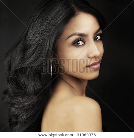 Beautiful young woman's face and long dark shiny hair.