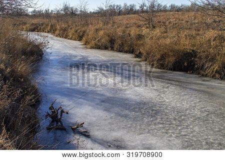 Frozen Creek Through Brown Grass And Trees, Rural Kansas