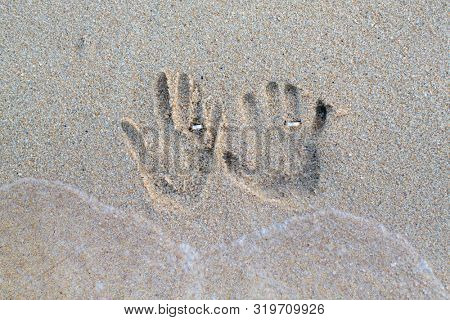 palm prints of newlyweds in the sand with wedding rings