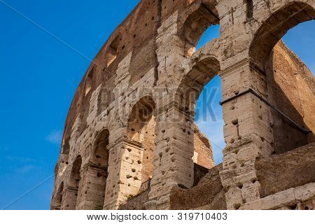 Detail Of The  Facade Of The Famous Colosseum Or Coliseum Also Known As The Flavian Amphitheatre In