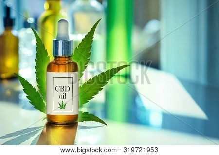 Cbd Oil Glass Bottle, Tincture And Hemp Leaf On A Background Of A Medical Laboratory. Concept Of Leg