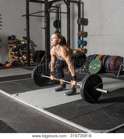 Strong female weight lifter preparing to lift barbell.