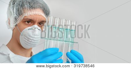 Keen Adult Male Scientist In White Gown And Protective Nitril Gloves Holding Glass Tubes With Chemic
