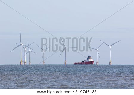 Renewable Energy Offshore Wind Farm Turbines With Passing Maintenance Supply Vessel Ship. Windfarm O