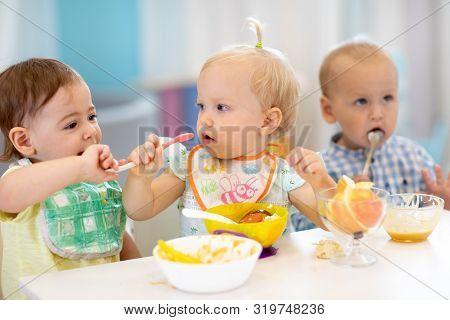 Babies Have Lunch In Creche. Kids Eating Healthy Food In Kindergarten. Funny Children Have A Dinner
