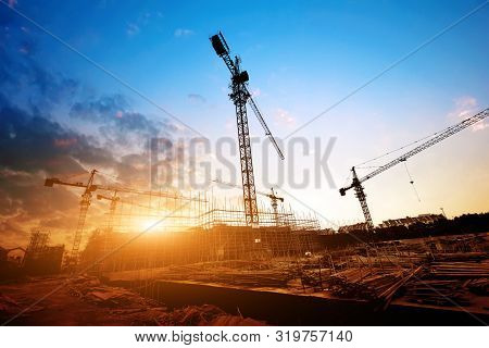 Construction Site, Silhouettes Of Construction Industry Workers On Scaffolding Against The Sunset Li