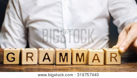 A Man Puts Wooden Blocks With The Word Grammar. Set Of Structural Rules Governing The Composition Of