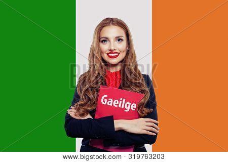 Love Irish Concept. Happy Cute Woman With Irish Flag. Book With Inscription Irish On Irish Language