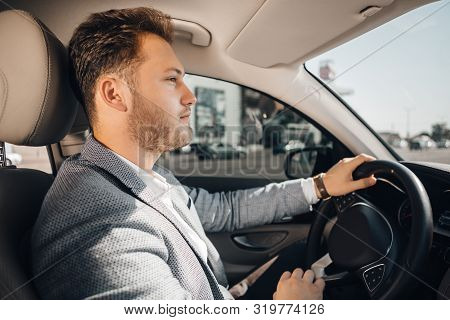 Successful Businessman In A Suit Drives His Luxary Car.