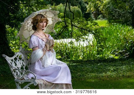 Beautiful Lady In Vintage Dress Sitting On Ornate Metal Bench Holding Parasol Next To River