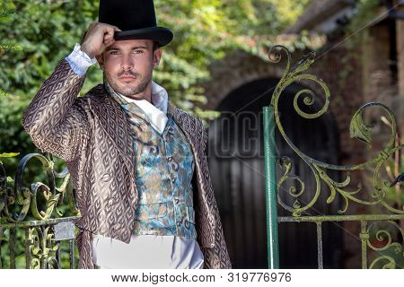 Portrait Of Attractive Gentleman Dressed In Vintage Costume, Holding Top Hat In Stately Home Courtya