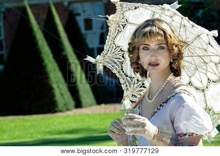 Beautiful Woman In Vintage Clothing Sitting On Lawn In Front Of Stately Home Holding Parasol And Dri