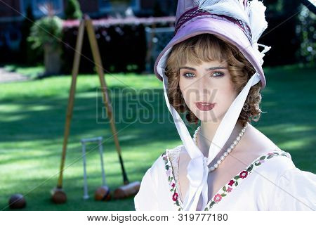 Beautiful Woman In Vintage Georgian Dress And Bonnet Sitting In Front Of Georgian Mansion With Croqu