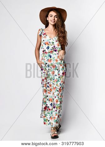 poster of Luxurious young slim girl with long hair in a long dress with a floral print and a straw hat. Getting ready is going on a date on a warm summer evening.
