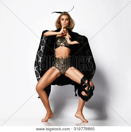 Young Sports Girl Shaman In Dark Gold Lingerie And A Black Cloak, With A Bandage On Her Knee And Fea