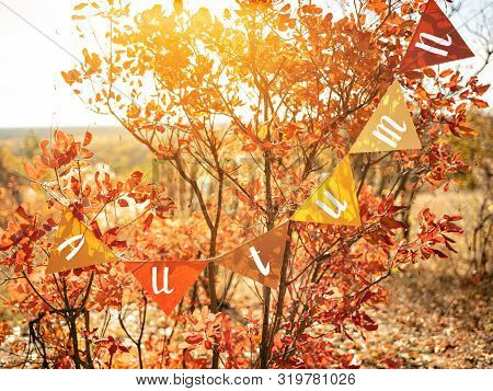 Welcoming Garland With Title Autumn On Glistening Autumn Foliage. Orange And Red Vibrant Leaves In S