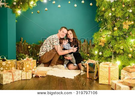 Young Family Celebrates New Year. The First Christmas Of A Newborn With A Baby. Young Family Celebra