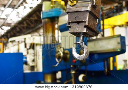 Crane Hook Of The Overhead Crane In The Workshop Of An Industrial Plant.  Push Remote Control Switch