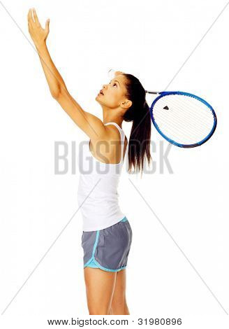 Healthy active mixed race female throws an imaginery tennis ball in the air and pretends to serve in studio