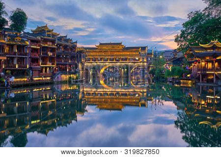 poster of Chinese tourist attraction destination - Feng Huang Ancient Town (Phoenix Ancient Town) on Tuo Jiang River illuminated at night. Hunan Province, China