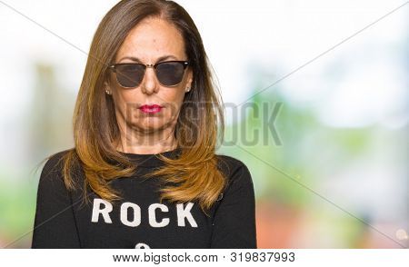 Beautiful middle age woman wearing sunglasses and rock and roll sweater skeptic and nervous, disapproving expression on face with crossed arms. Negative person. poster