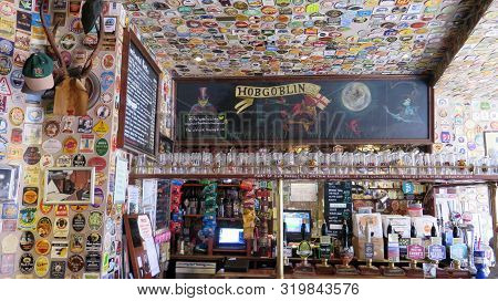 Variety Of Beer Coasters Adorn Walls And Ceiling In English Pub