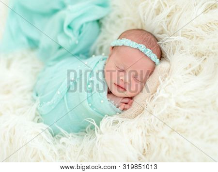 Sleeping adorable newborn baby child, in blue colored blanket and with floral headband