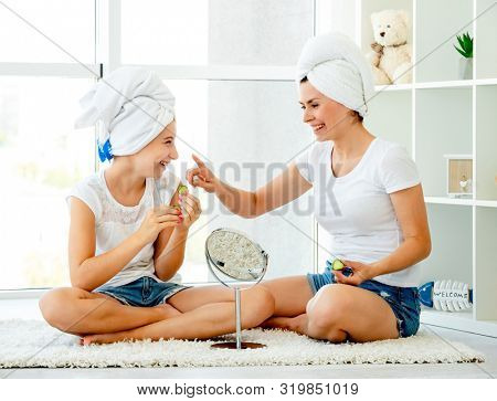 Lovely mother and daughter making spa procedures in the bathroom, using cucumber, in front of little mirror