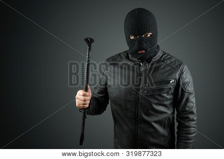 Robber, Bandit In A Balaclava With A Crowbar In His Hands On A Black Background. Robbery, Hacker, Cr