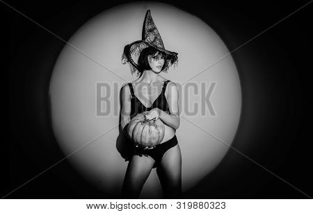 Woman In Witch Halloween Costume With Halloween Hat Standing Over Red Night Light Background. Beauti