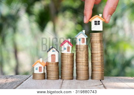 poster of Money savings, investment, making money for future, financial wealth management concept.Woman's hand holding the house. Concepts for stairs, real estate, mortgages and real estate investments.